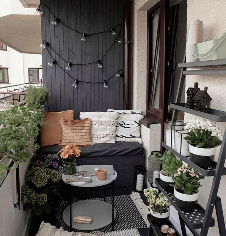 Come arredare un piccolo terrazzo coperto, divano con panchina e cuscini, parete di legno con fili di lampadine