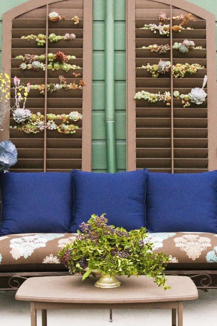Divano da esterno con cuscineria, tavolino di legno con vaso, come arredare un piccolo terrazzo coperto