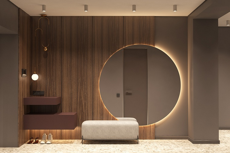 arredare corridoio ingresso parete con pannelli di legno specchio rotondo con retro illuminazione