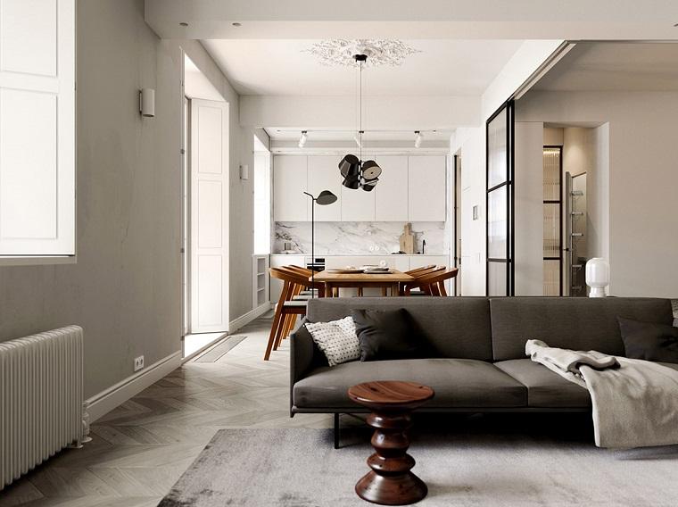 arredare mini appartamento open space soggiorno e cucina divano grigio con tavolino di legno rotondo