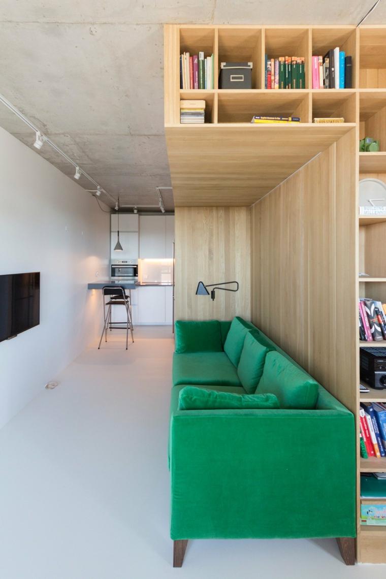 come arredare un monolocale di 50 mq soggiorno con divano verde libreria di legno con mensole