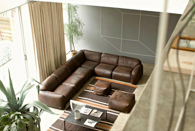 Soggiorno moderno, salotto con divano di pelle, parete grigia con disegno di un quadrato tridimensionale