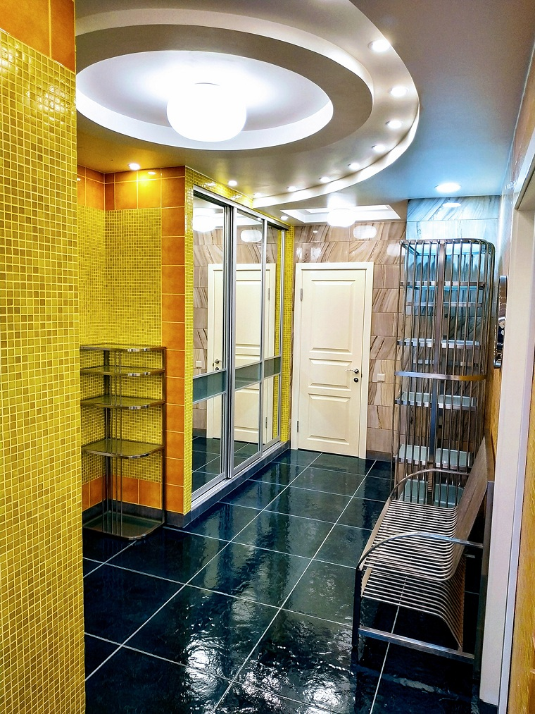 pareti con piastrelle gialle pavimento nero pannello appendiabiti da parete illuminazione con lampadario