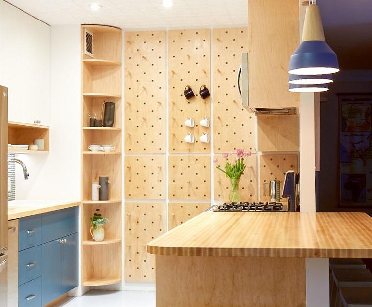 cucina agolare con penisola come tavolo da pranzo parete con pannello di legno e ganci