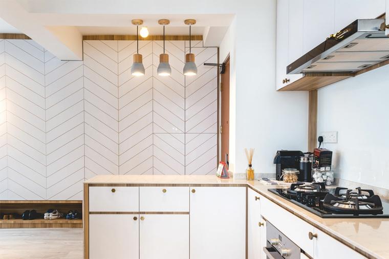 cucina bianca con isola illuminazione con tre lampade paraschizzi di colore bianco