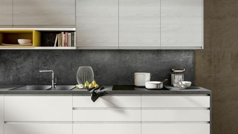Cucine moderne bianche, parete paraschizzi di colore grigio, top di colore grigio