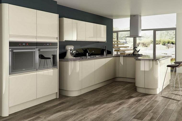 cucina con penisola mobili laccati colore beige pavimento legno elettrodomestici