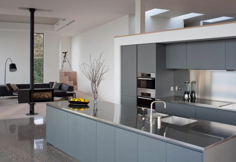 Cucina con isola centrale di colore grigio, open space soggiorno e cucina