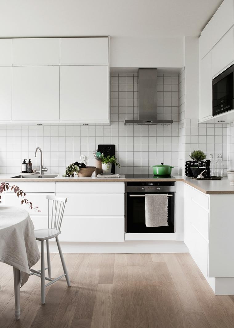 rivestimento parete in cucina con piastrelle bianche tavolo da pranzo rotondo