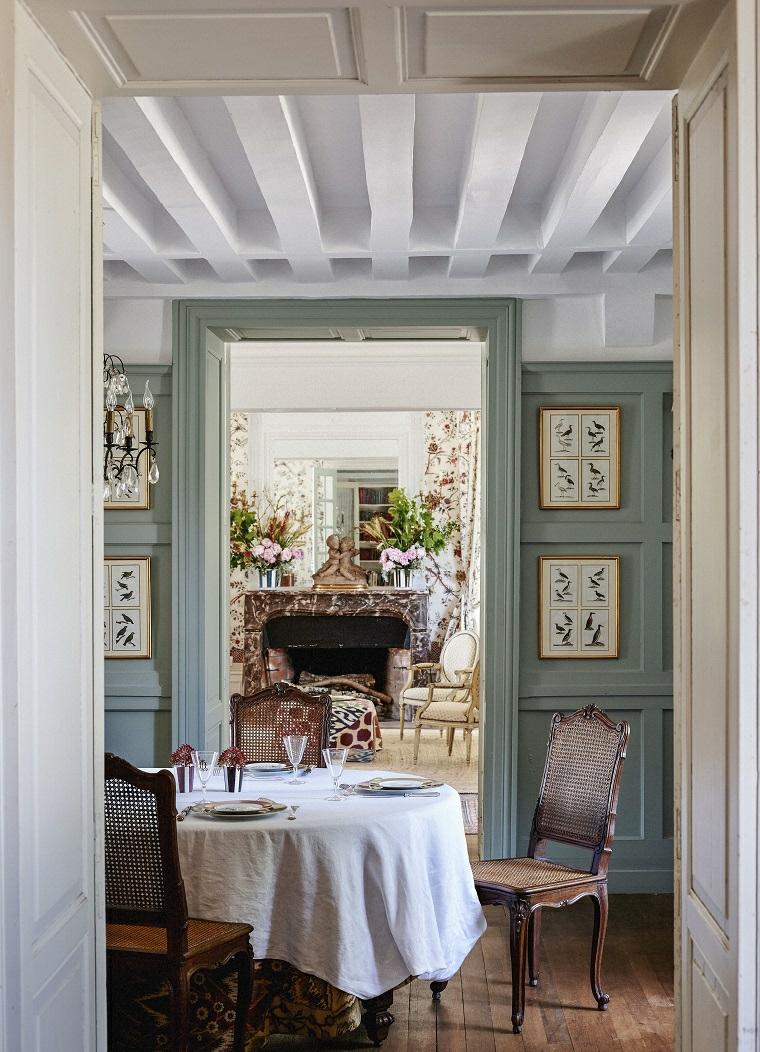 sala da pranzo con tavolo rotondo soffitto con travi parete decorata con quadri