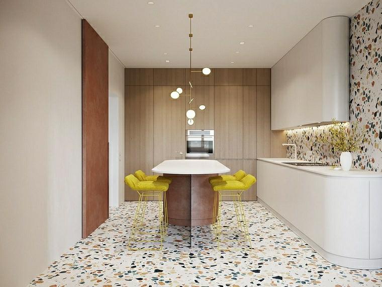 angolo cottura cucina con parete rivestita in piastrelle colorate tavolo da pranzo con sgabelli alti