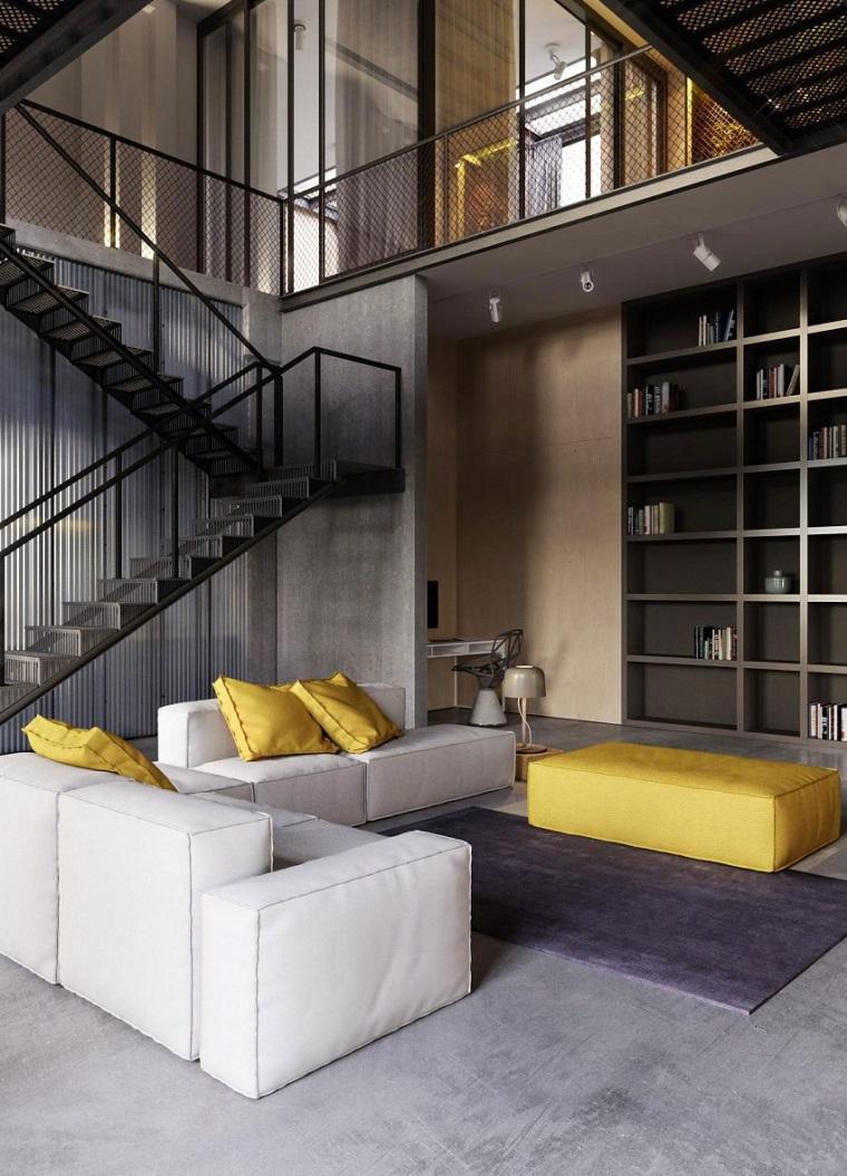 Loft con scale interne, divano con cuscini gialli, arredamento industriale