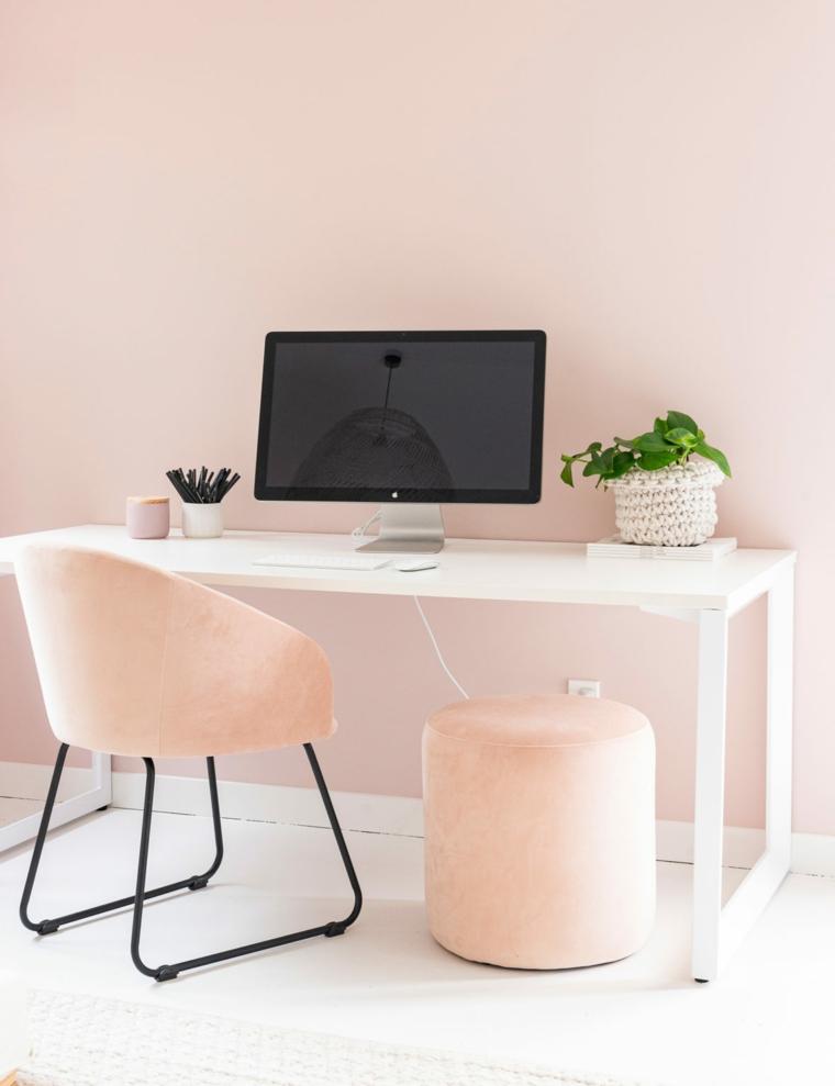 Ufficio in casa con scrivania e poltrona, parete dipinta di colore rosa, scrivania con computer