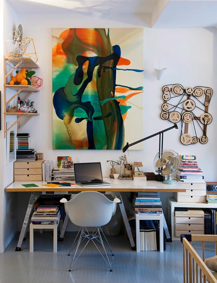 Ufficio in casa, scrivania con libri, parete decorata con quadro, arredo industrial moderno