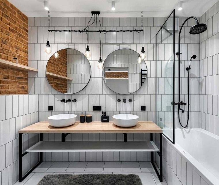 Arredamento industriale, bagno con vasca e due lavandini, pareti rivestite con piastrelle bianche