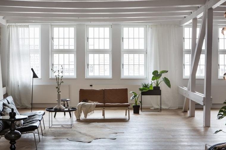 Soggiorno con travi di legno in mezzo, arredamento moderno e arte povera insieme