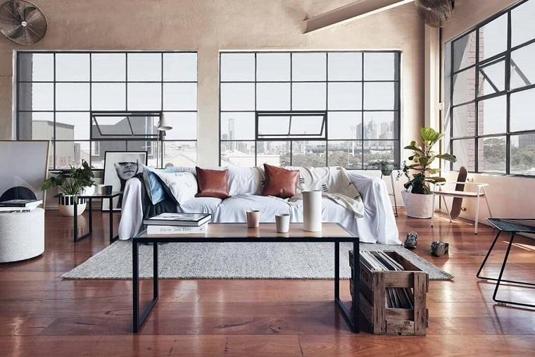 Soggiorno con divano e tavolino, arredamento stile industriale, pavimento in legno con tappeto