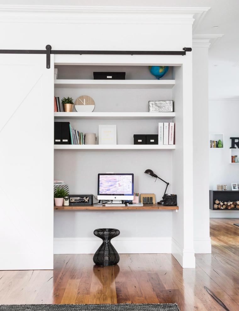 Ufficio con porta scorrevole, parete bianca con mensole, scrivania con computer