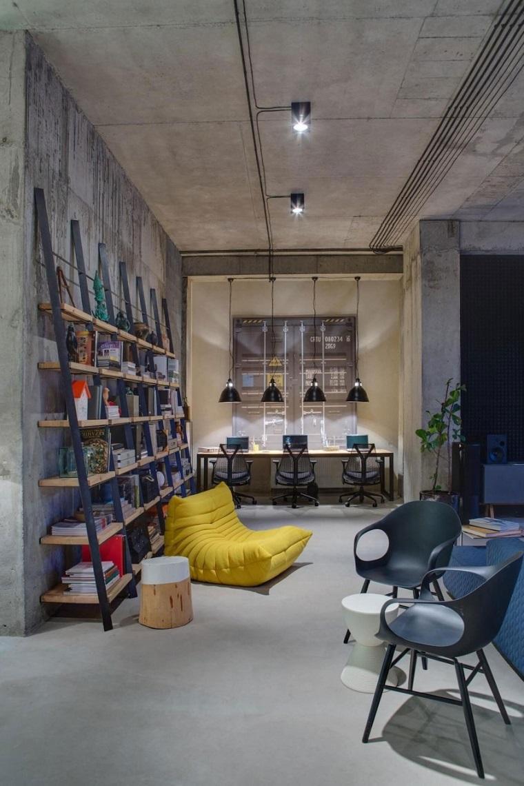 Casa stile industriale moderno, parete con libreria scaffali aperti, arredamento con sedie e poltrona