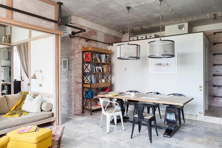 Arredamento stile industriale, tavolo da pranzo in legno con sedie, parete con mattoni a vista