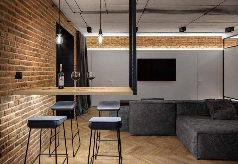 Arredamento industriale, soggiorno con divano grigio angolare, rivestimento parete con mattoni a vista