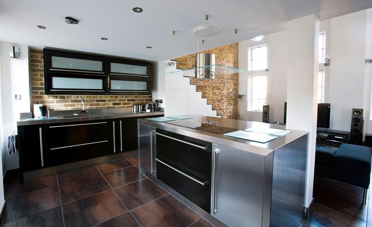 cucina-acciaio-inserti-neri-parete-muratura