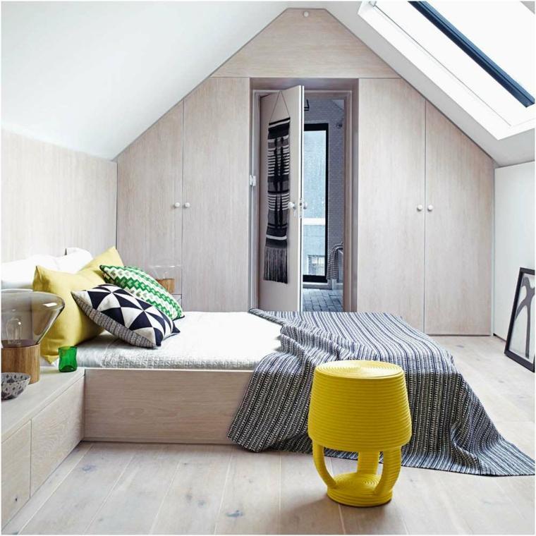 Zona notte in mansarda, sedia colore giallo, soffitto in pendenza, camere matrimoniali moderne