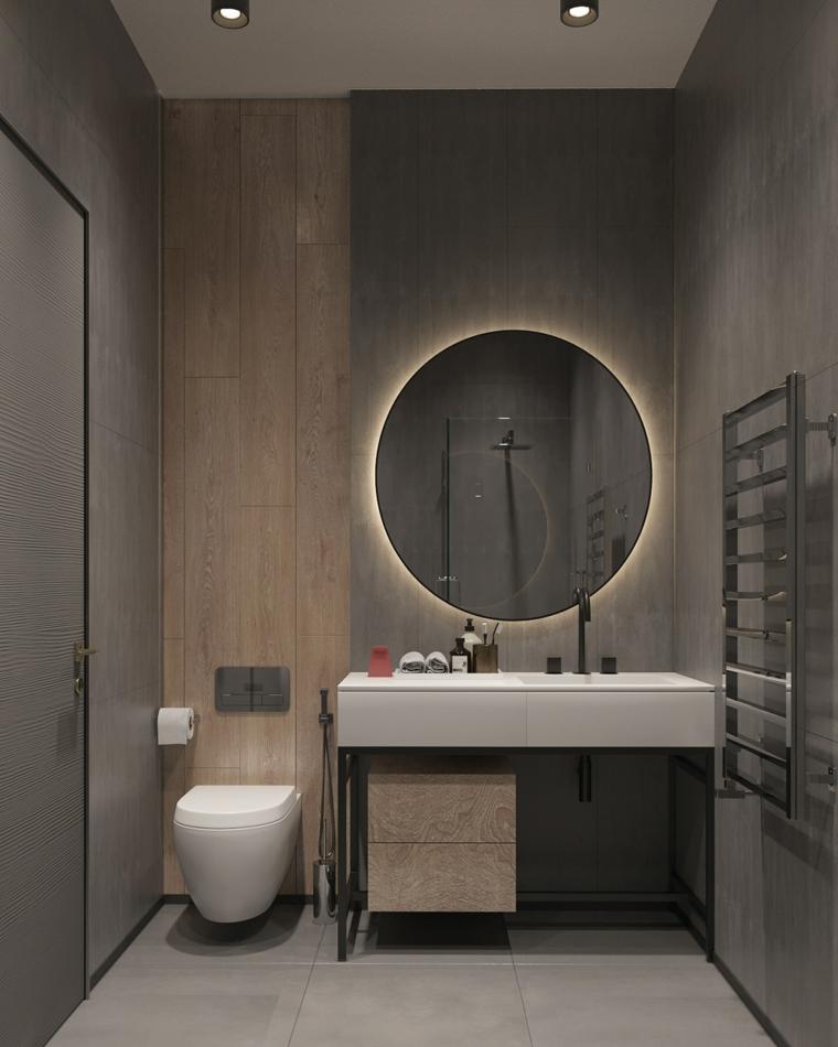 Arredamento bagno con mobili di legno, specchio rotondo con retro illuminazione