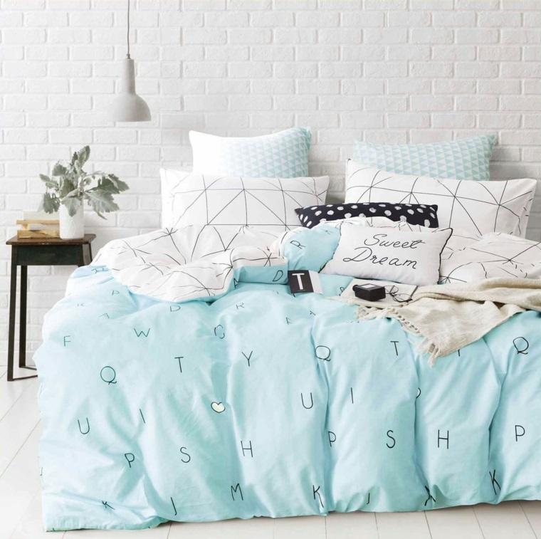 Letto con biancheria colorata, cuscini con scritte, parete effetto pietra, lampada sospesa, come pitturare una stanza