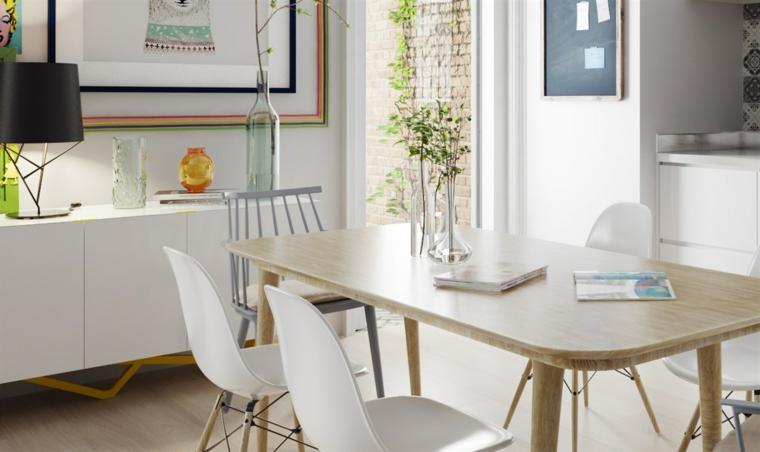 Sala da pranzo con tavolo di legno, mobile di colore bianco, decorazione parete con quadri
