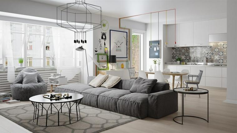 Open space soggiorno cucina, divano di colore grigio, lampade sospese da soffitto