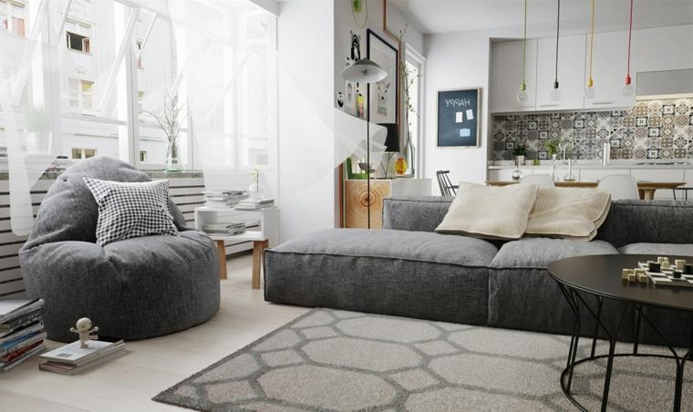 Soggiorno con divano di colore grigio, pouf poltrona, salotto con tappeto geometrico