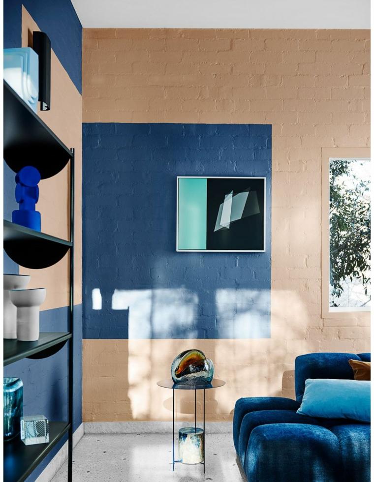 arredare piccoli appartamento divano blu tessuto libreria parete carta da parati mobile tavolino