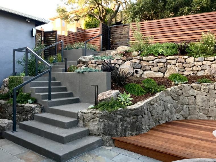 decorazione giardino con recinzione in sassi pavimento in legno