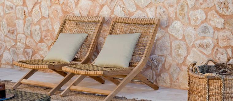 giardino con parete in mattoni mobili in raffia da esterno con cuscini grigi