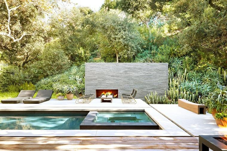 giardino di casa con piscina rettangolare arredo con sdrai di rattan