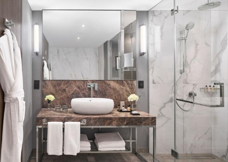 sala da bagno lavandino piastrelle marmo specchio box doccia vetro lampade