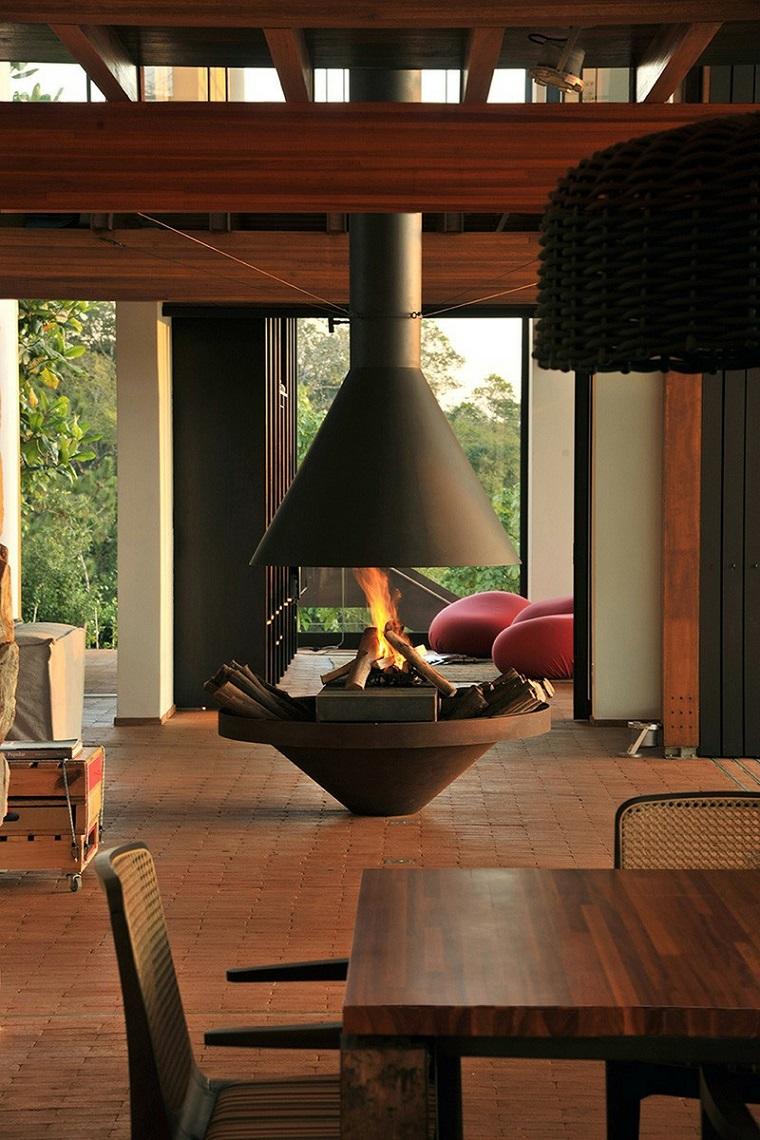 camino-rustico-metallo-forma-originale-tavolo-legno-design-lampadario-sospensione