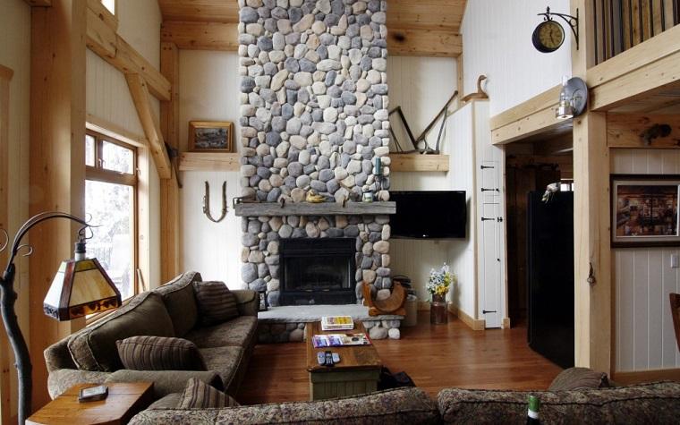 camino-rustico-travi-legno-pavimento-scuro-decorazioni-parete-orologio-metallo-originale