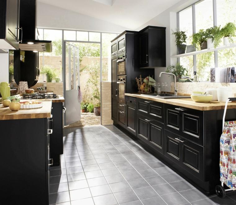 cucina-colore-nero-mobili-legno-cappa-piantine-pavimento-grigio-giardino