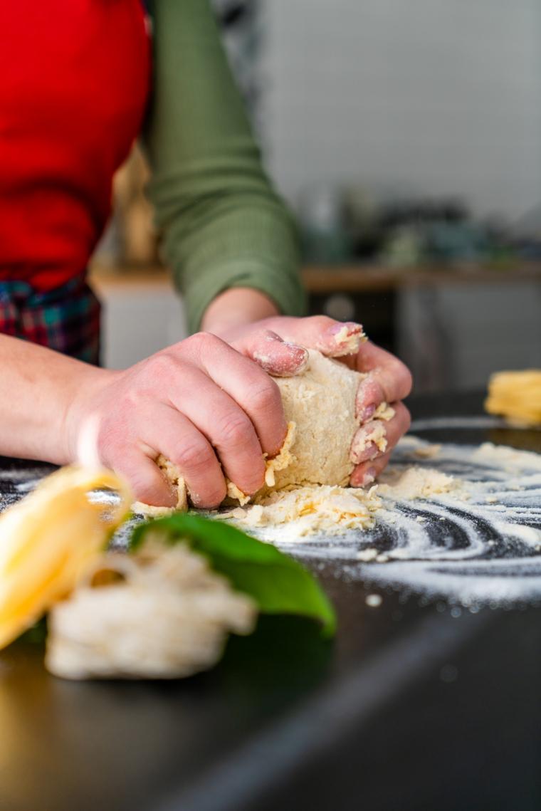 Donna che sta lavorando un impasto, tagliatelle all'uovo fatte in casa