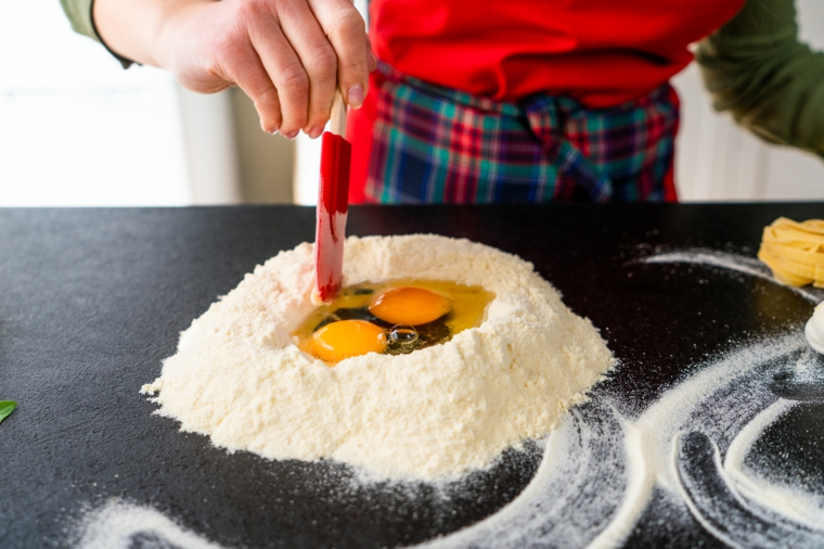 Uova rotte nella farina, tagliatelle fatte in casa, pasta fresca con uova