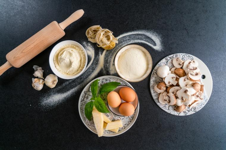 Ingredienti in ciotole e piatti, pasta fresca ricetta, gli ingredienti per fare le tagliatelle