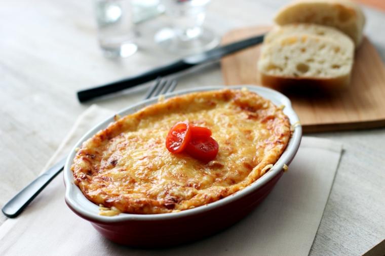 primi-piatti-sfiziosi-moussaka-sfornato-teglia-tavolo-legno-pane-pomodorini