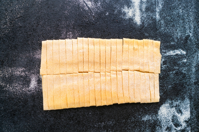Tagliatelle all'uovo con pasta fresca, tagliatelle su un piano di lavoro con farina