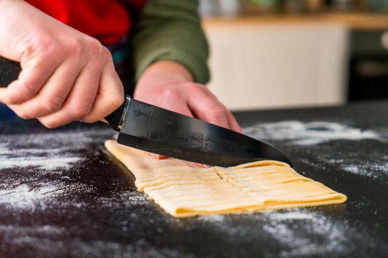 Donna che taglia la pasta fresca con coltello, sughi per tagliatelle fatte in casa