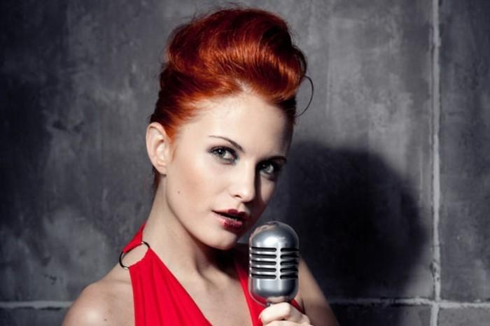 acconciatura-anni-50-donna-capelli-rossi-vestito-microfono-retrò-parete-grigia