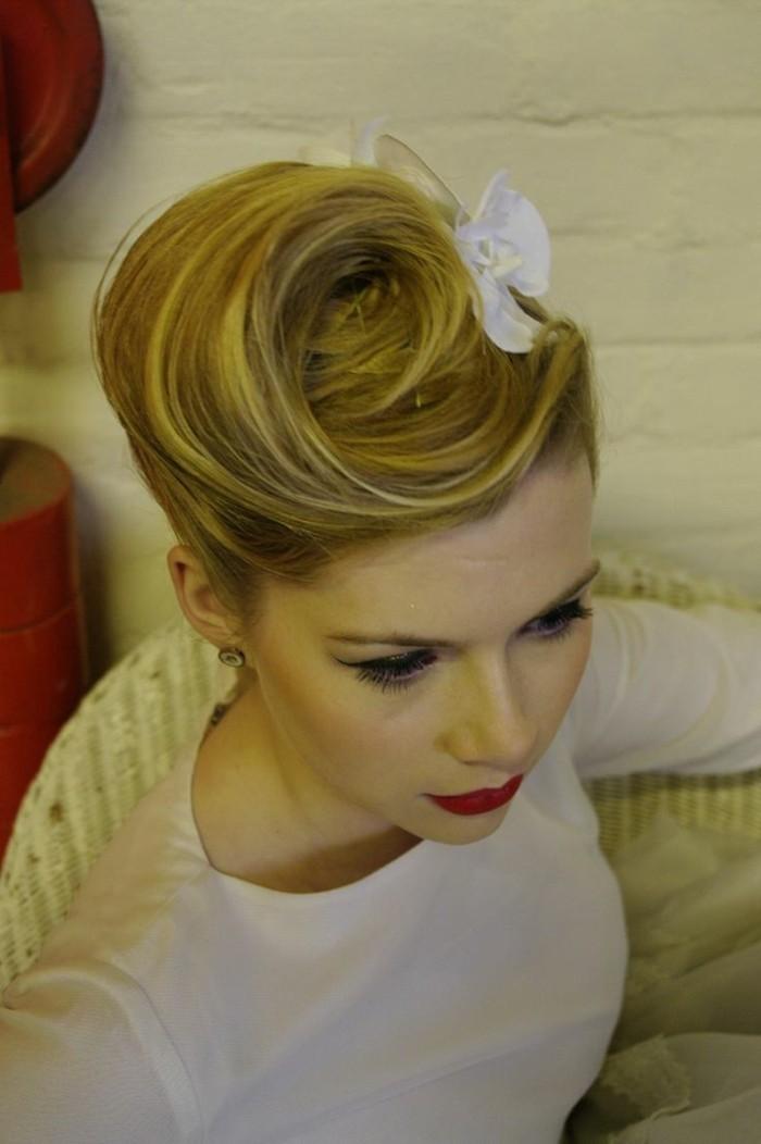 acconciature-anni-50-donna-capelli-biondi-legati-fiore-bianco-vestito