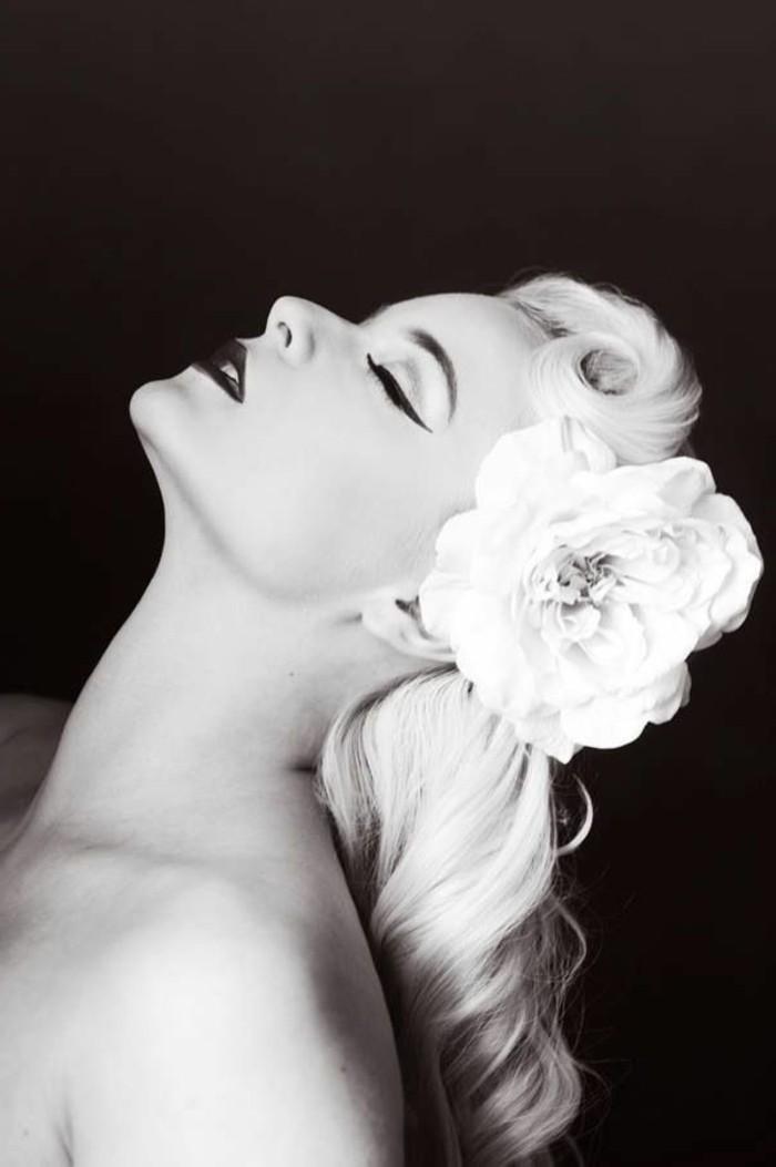 capelli-anni-50-donna-capelli-biondi-boccoli-fiore-bianco-sfondo-colore-nero