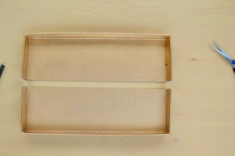 Tagliare una scatola di cartone in due parti, scatola di cartone accanto a delle forbici